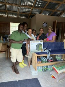 Group with pictured with food and supplies for the people of Haiti
